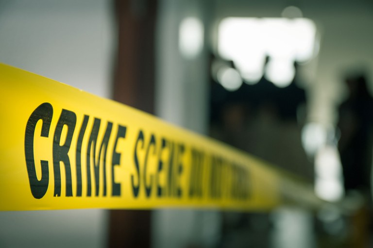 A stock image of crime scene tape and investigators in the background.