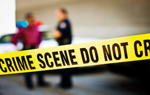Crime scene tape with two police officers and a police vehicle in the background. © iStockphoto.com