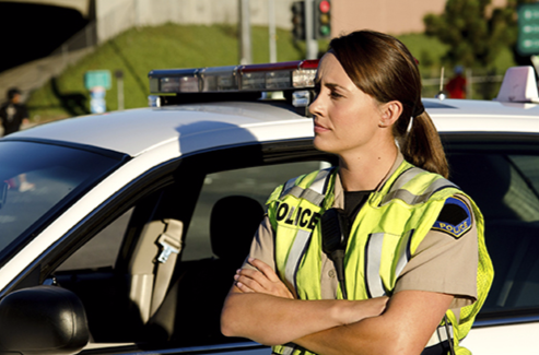 A police officer stands next to her car while wearing a safety vest.