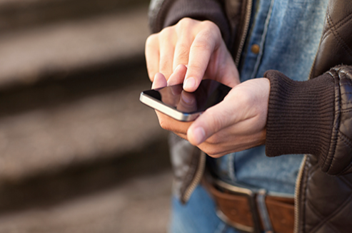 Stock image of a man checking his smartphone for messages.