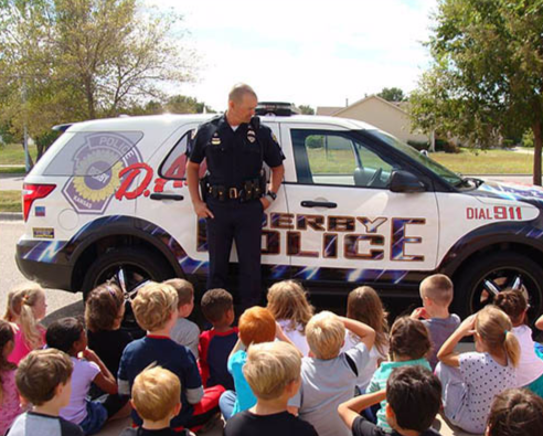 A police officer discusses the dangers of drug use with a group of students.