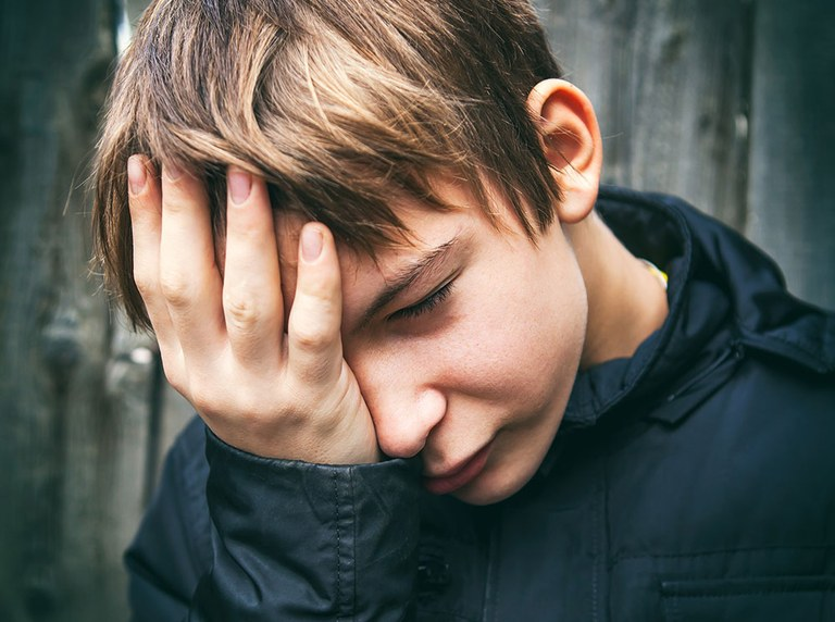 A stock image of a depressed and sad young boy.