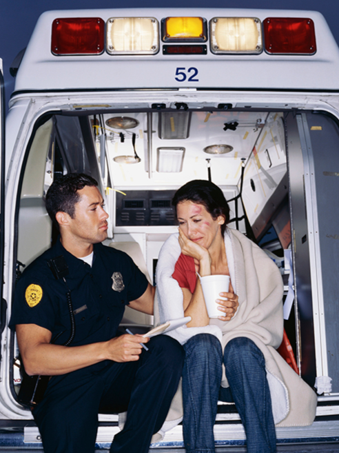 A victim of domestic violence is comforted by a police officer in the back of an ambulance.