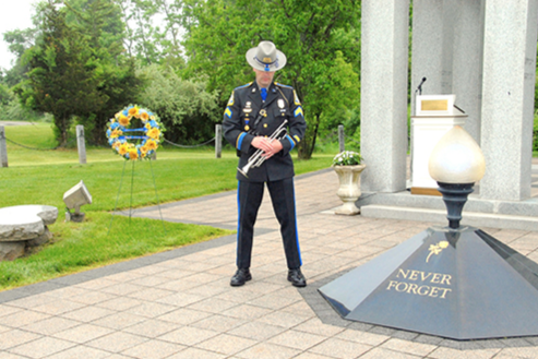 Depiction of an officer next to the eternal flame at the Connecticut Law Enforcement Memorial.
