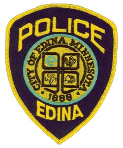 The patch of the Edina, Minnesota, Police Department shows the rich history and traditions of the town that the department serves. The central image displays the city's seal, which it adopted in 1974. The seal recalls the Irish and Scottish immigrants who first settled in the community, as well as the mill they used to process their crops. The cloverleaf design that encompasses these symbols follows the general pattern of the city's major highways. Below the image, the patch displays 1888 as the city's year of incorporation.