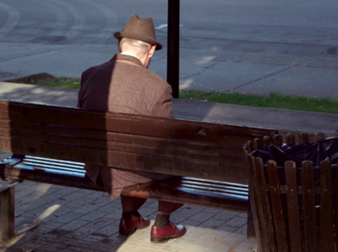 An elderly man sits on a park bench, waiting.