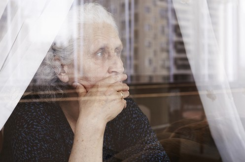 Stock image of an elderly woman looking out a window with her hand on her mouth.