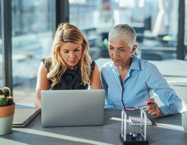 Stock image of an older business woman training a younger, new employee.