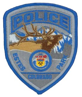 The Estes Park, Colorado, Police Department patch highlights the town's location as the gateway to the 265,000–acre Rocky Mountain National Park. Each summer the park receives over 3 million visitors who tour the majestic and rugged mountain peaks and valleys. The patch features one of the area's most abundant wildlife species, the 5-point bull elk, with snow-capped Rocky Mountains in the background and the Colorado State seal in the foreground.