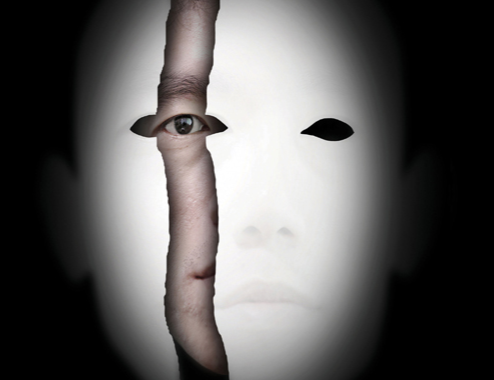 Stock image of a face peers out from behind the mask of psychopathy.