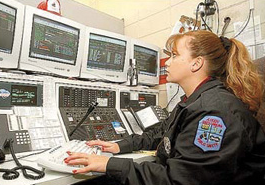 A female police officer performs dispatcher duties.
