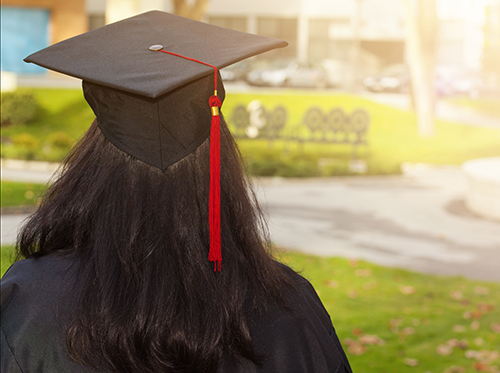 A young woman is depicted at their graduation ceremony.