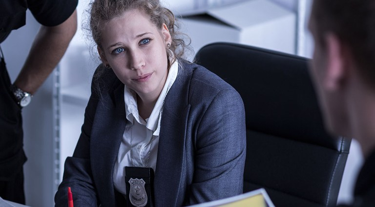 Stock photo of a female officer intently listening to a co-worker.
