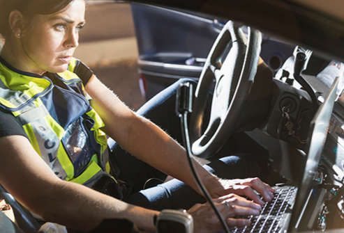 A female officer is depicted typing on a dashboard-mounted laptop in her police vehicle.