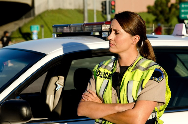 A stock image of a female police officer standing next to a patrol car.