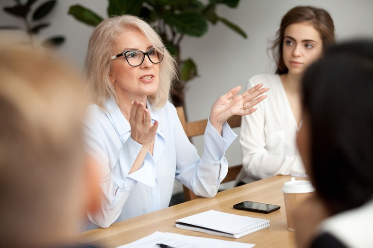 Stock image of a female speaking at a business meeting.