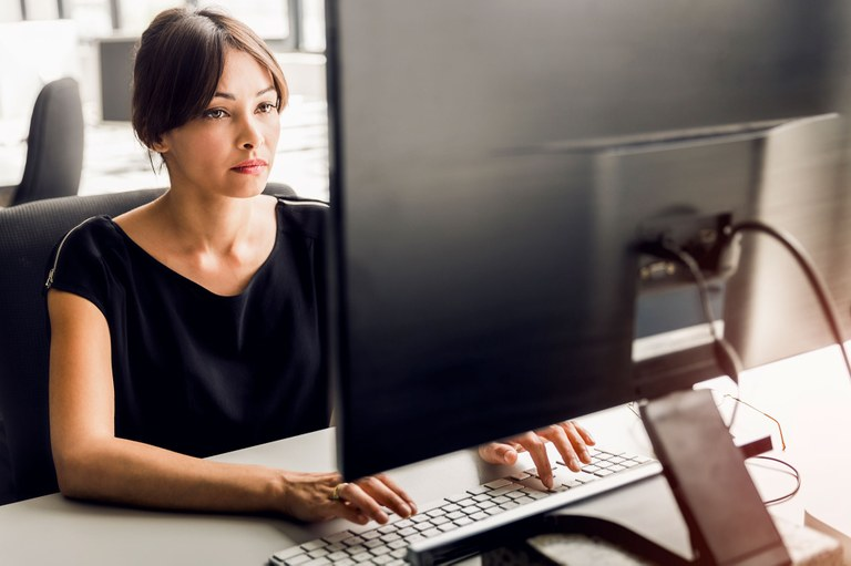 A stock image of a female working on a computer.