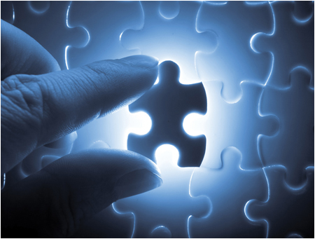 Stock image of a person holding a glowing puzzle piece on a puzzle. © Thinkstock.com.