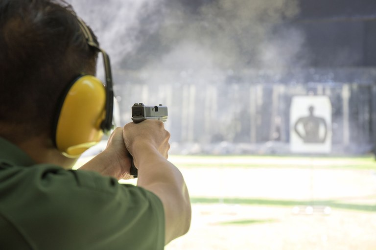 A stock image of a man at a firearms range target shooting.