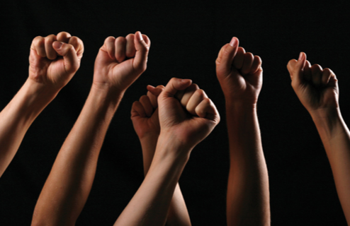 Stock image of six fists raised in protest.