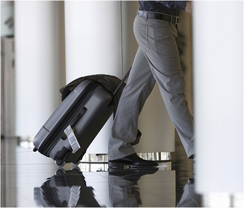 A man pulling a suitcase in an airport or hotel.