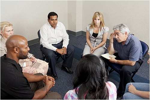 Stock image of six people in a meeting.