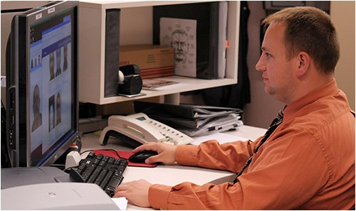 An FBI employee at the Criminal Justice Information Services Division at his desk looking at a computer monitor.