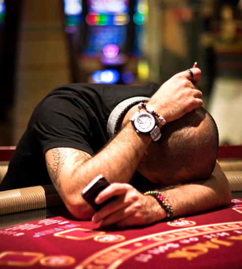 An obsessive gambler rests his head on a black jack table having lost all his money.