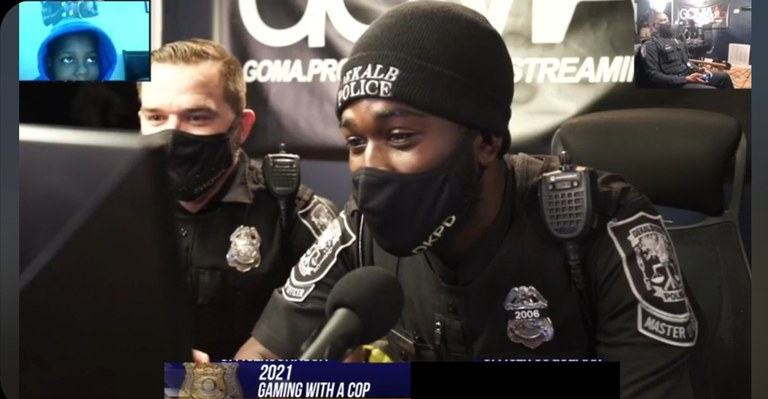 An image of two DeKalb County officers playing video games online.