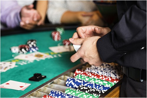 Stock image of a gambling table at a casino with a card dealer and two players.