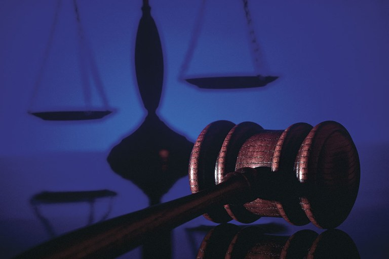 A stock image of a gavel and the scales of justice in the background.