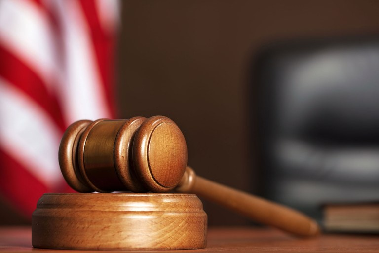 Stock image of a gavel in a courtroom setting with the American flag in the background.