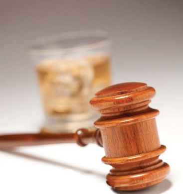 Gavel with Glass of Whiskey in Background (Stock Image)