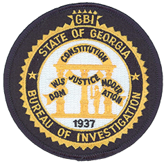 The Georgia Bureau of Investigation patch consists primarily of the state's seal. Three pillars supporting an arch are emblematic of the three branches of government—legislative, judicial, and executive. A sentry stands with a drawn sword, defending the state constitution and its principles of wisdom, justice, and moderation. The name of the agency surrounds the seal. The colors of gold and blue represent courage and loyalty.