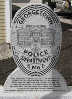 The monument, designed after the Georgetown Police Department badge, is made of Vermont granite. In the center of the monument is the Georgetown Town Hall, the American flag, the state flag, and the seal of Massachusetts.