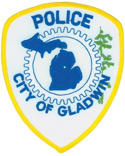 At the right of the patch of the Gladwin, Michigan, Police Department, a cedar tree represents the logging industry, as well as the fact that the city of Gladwin originally was called the village of Cedar. The gear represents the industrial nature of the area. Also featured is a silhouette of the state of Michigan with the location of Gladwin identified.