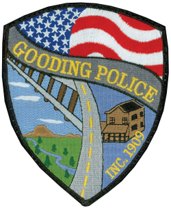 Idaho State Highway 46 runs through the center of the Gooding Police Department patch, as it does the city of Gooding itself. The century-old Gooding Hotel is depicted on the right side of the patch, while the left side depicts the Little Wood River that runs through the city, shadowed by the railroad tracks of the Union Pacific mainline. Above all is the American flag, which stands for the city's devotion to safeguarding the freedoms of the nation.