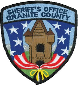The Granite County, Montana Sheriff's Office is housed in the tower of the county jail, in continuous use since it was built in 1896, depicted in the center of the patch. The flag tied with the yellow ribbon shows patriotism and support for men and women serving in the military. The mountains, blue sky, and green grass represent the area's beauty and cleanliness.