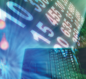 Stock image of numerical data moving above a laptop across an endless continuum of information. © Thinkstock.com