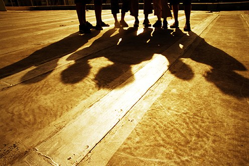 Stock image showing a group standing outside and their shadows on the ground.