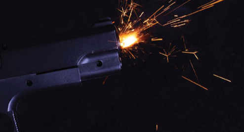 Sparks fly as a gun fires into the night.