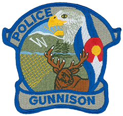 The patch of the Gunnison, Colorado, Police Department features an eagle—draped by the Colorado flag—symbolizing the nation, as well as liberty and freedom. The Rocky Mountains sit in the background. A w, the largest single letter in the Western Hemisphere, represents Western State College, located in the city. The fields refer to the ranching industry that still thrives in the valley. An elk, Gunnison's symbol, represents the hunting and outdoor activities the area is known for.