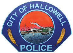 The patch of the Hallowell, Maine, Police Department is based on the city's seal, illustrating the area's commerce in the 1800s. In the center of the seal, a train is shown transporting valuable granite. Also, two ships are depicted in the Kennebec River, representing both the shipbuilding industry and the transport of goods that made Hallowell a very active port in central Maine.