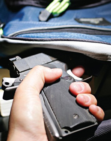 A person pulling a handgun out of a backpack.