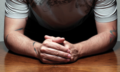 A suspect clasps his hands on a table. © Thinkstock.com.