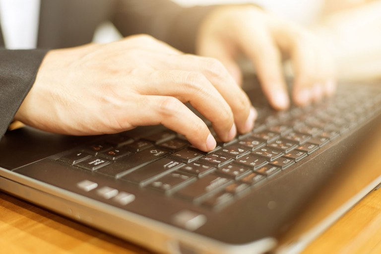 Stock image of a man's hands typing on a computer keyboard.
