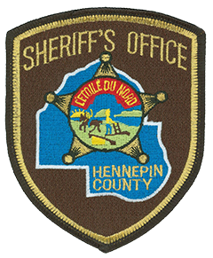 "The center of the Hennepin County, Minnesota Sheriff's Office patch features the state's seal, which depicts a pioneer plowing and a Native American riding into the sunset. The motto L'etoile du' nord translates to ""the star of the north,"" referring to Minnesota's status as ""The North Star State."""