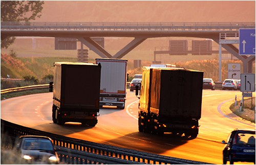 Stock image of a highway scene with various cars and trucks.