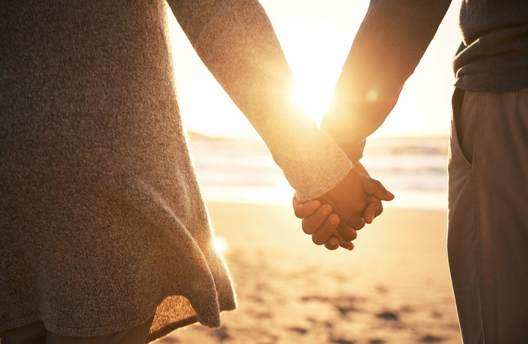 A stock image of a couple holding hands.