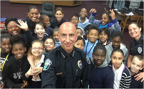 Chief Sanchez and other officers of the Hollywood, Florida, Police Department with a group of kids as part of the Cops Mentoring Kids program.